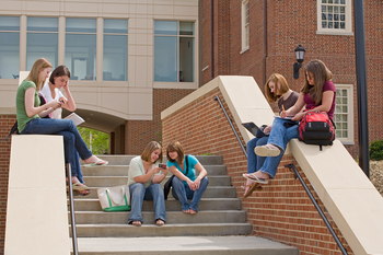 Female high school students sit on the campus stairs