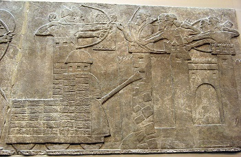 Relief of Assyrians attacking town with siege engines