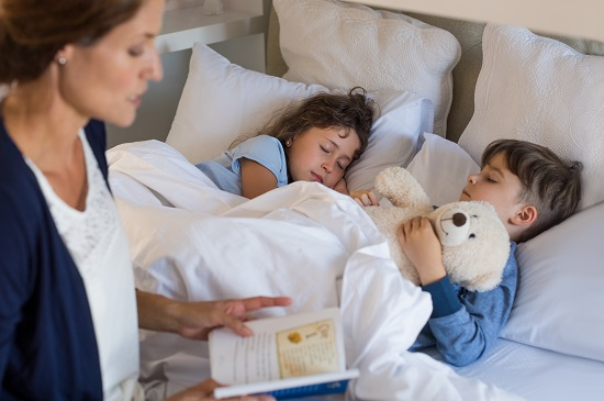 Parent reading a bedtime story to her kids
