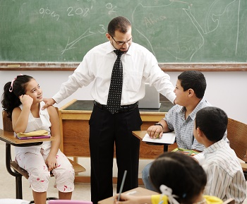 Teacher interacting with students in the classroom.