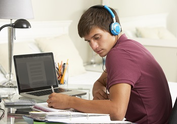 male student studying for AP test via podcast