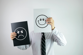 employee holding up smiley face to indicate happiness and loyalty