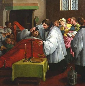A priest anoints a sick person.