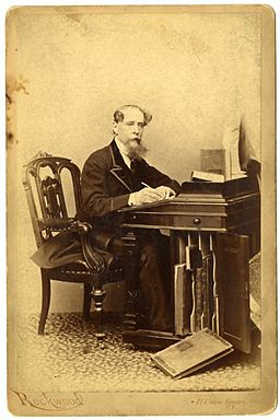 Charles Dickens sitting at a desk.