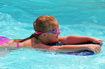A child swimming with a kickboard