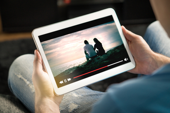 A person watches a movie on a tablet