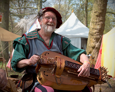 Photograph of man playing hurdy-gurdy