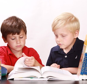 Two children reading a book.