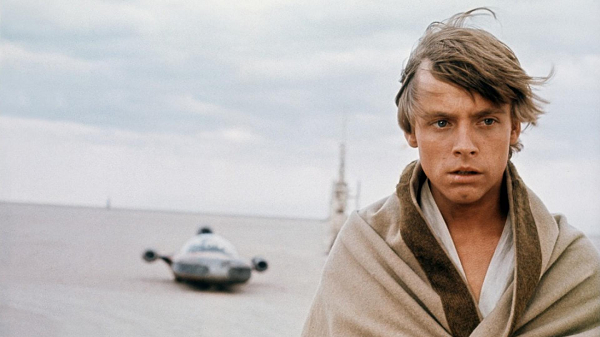 Movie still of Luke Skywalker surveying his wrecked home on Tatooine