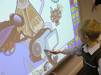 A young student interacting with an electronic whiteboard.