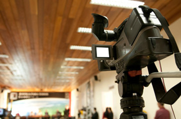 Video camera set up in the back of a lecture hall, recording the lecture.