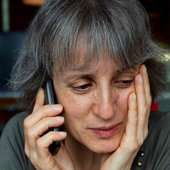 Image of woman struggling to understand on the phone.