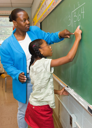 Teacher helping student with math on a blackboard